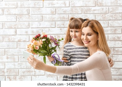 Woman taking selfie with bouquet of flowers received from her daughter for Mother's Day