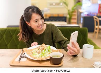 Woman taking selfie by cellphone in restaurant