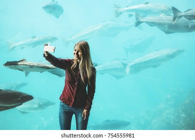 Woman taking selfie by smartphone at big aquarium fish Travel Lifestyle concept modern technology