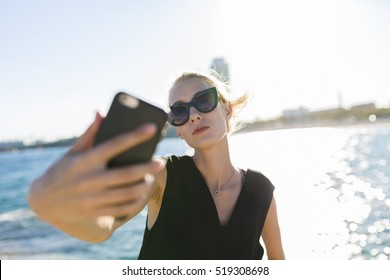 Woman taking a selfie with cell phone by the sea