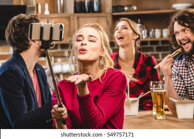 Woman taking selfie with her friends during home party