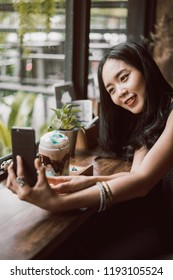 woman taking a selfie with a ice chocolate for her food blog.