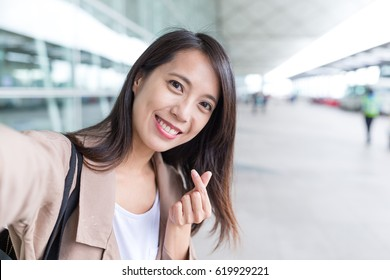 Woman taking selfie with korean style heart finger gesture