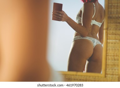 Woman taking selfie with mirror reflection in lingerie
