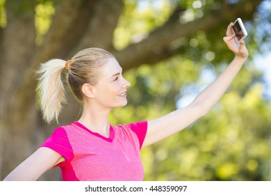 Woman taking selfie with the mobile phone in park