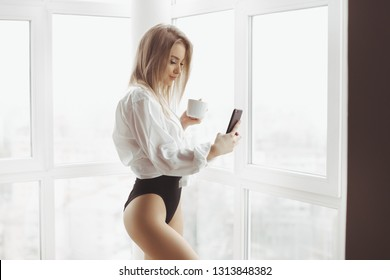 Woman taking selfie. Pretty blonde girl standing near window at home with cup of coffee or tea and smartphone in hands. Attractive sexy woman wearing white man's shirt drinking and looking at her