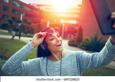 Woman taking selfie with tablet in park, making expression in sunset