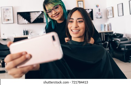 Woman taking a selfie using mobile phone with her hair stylist while sitting on salon chair. Woman in cheerful mood at the spa looking at mobile phone with her hair stylist.
