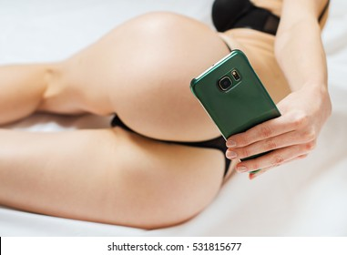 Woman taking sexual photo of herself with mobile phone.