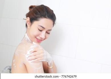 Woman taking a shower enjoying with foam bath.