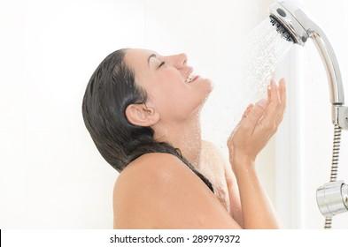 Woman taking a shower enjoying water splashing on her