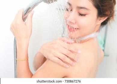 Woman taking a shower enjoying water splashing on her. selective focus