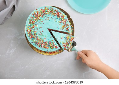 Woman taking slice of fresh delicious birthday cake at table, top view