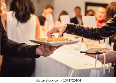Woman taking snacks from the waiter on a fashion event party. Catering service concept.