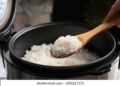 Woman taking tasty rice with spoon from cooker in kitchen, closeup