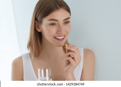 Woman taking vitamin pill with glass of fresh water indoors. Smiling girl taking omega 3 fish oil capsule, vitamin supplement. Diet nutrition concept