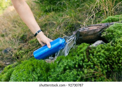 Woman taking water from mountain spring on hiking trip