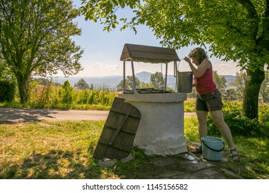A woman is taking the water from old, stone, water well  with a windlass and crank in the polish village. In the background view of the Cergowa Hill in the Low Beskids, Beskid Niski, Poland