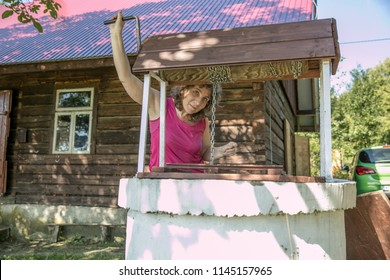 A woman is taking the water from old, stone, water well  with a windlass and crank in the polish village. In the background view of wooden, log house in the Low Beskids, Beskid Niski, Poland