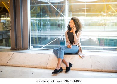 woman talking by mobile phone at the airport sitting at the window