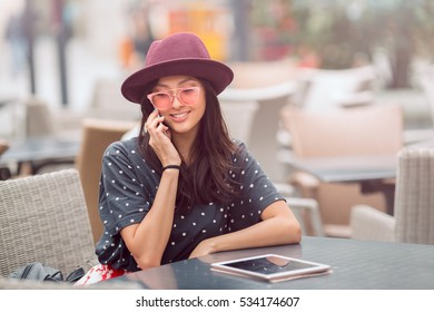 Woman talking by phone on lunch break in city cafe outdoors. Portrait of young smiling girl sitting with tablet pc and smartphone