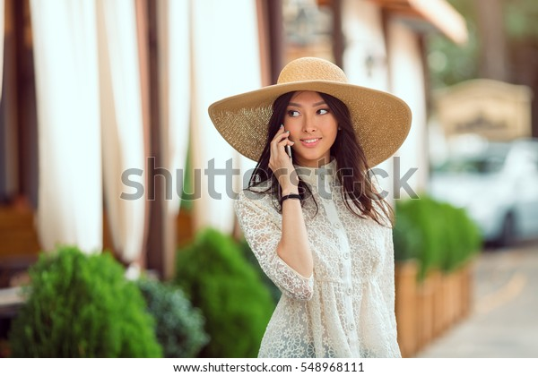 Woman talking by phone outdoors in city street. Portrait of young smiling fashion girl standing with smartphone