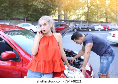 Woman talking by phone while her husband trying to fix damaged car