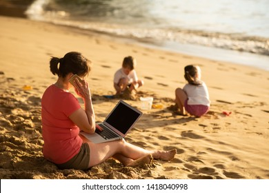 Woman talking to clients on phone, working on laptop. Kids playing with beach sand.
