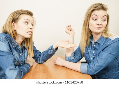 Woman talking with confident ignorant female friend being mad after quarrel, ignoring what she saying.