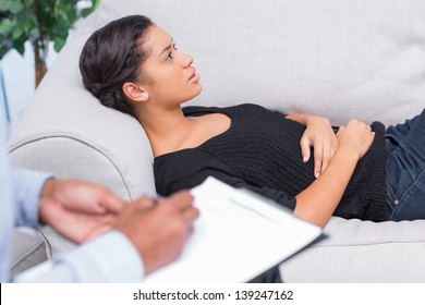 Woman talking during therapy session while therapist takes notes