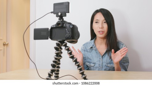 Woman talking in front of the digital camera with her for making vlog at home
