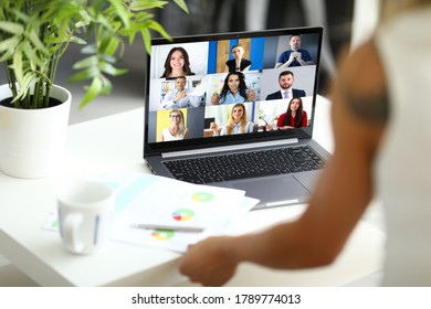 Woman talking with international colleagues using online video chat service at workplace closeup