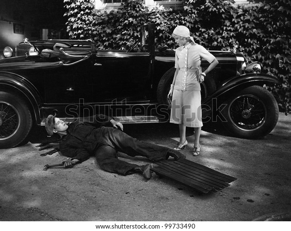 Woman talking to man working on car