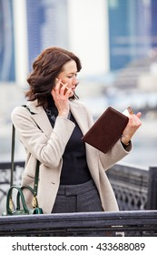 Woman talking on cell phone and looking at the business notebook outdoors