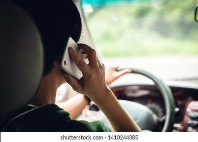 woman talking on cellphone when driving, concept of dangerous driver