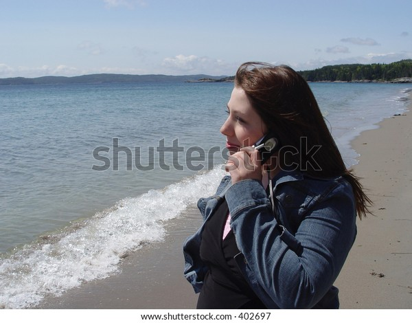 Woman talking on cellular phone on beach by the ocean