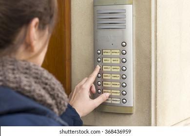 Woman talking on the intercom and presses the button