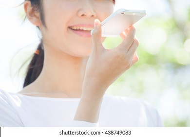Woman talking on a mobile phone , voice recognition , fresh green