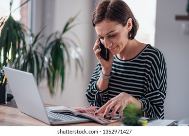 Woman talking on the phone and ordering cosmetics from the catalogue