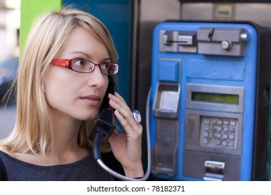 Woman talking on the phone in a retro phone boot