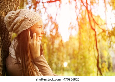 Woman talking on smart phone in the park autumn day.