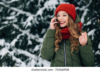 Woman talking on smartphone. Smiling girl in red winter hat and scarf talking on smartphone in cold winter day
