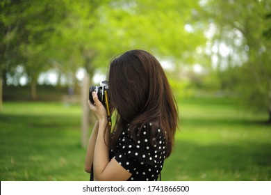 Woman talking a photo with film camera