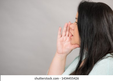 Woman talking rumors or whispering, holding hand near mouth. Side view on grey