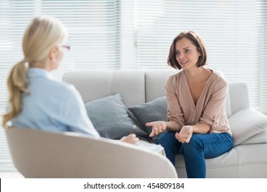 Woman talking to therapist on sofa at home