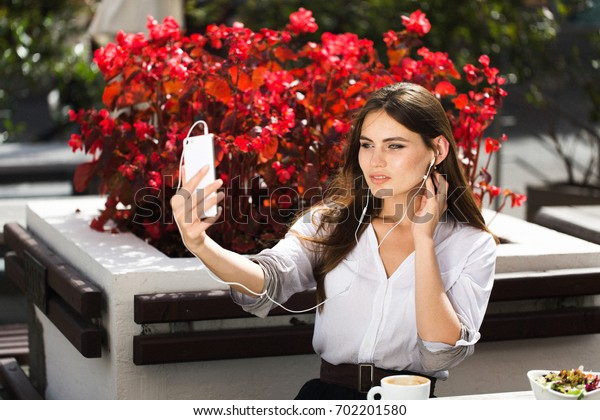 Woman talks via headphones on the phone
