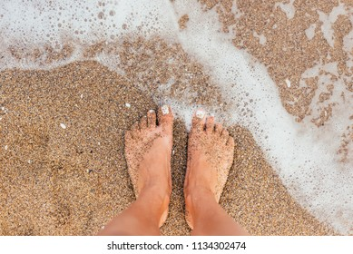Woman tanned legs on beach sea foam waves standing on sand, enjoying vacation, view from above, sun flare effect. Light warm pastel Toned.