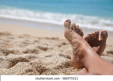 Woman tanned legs on sand beach. Travel concept. Happy feet in tropical paradise
