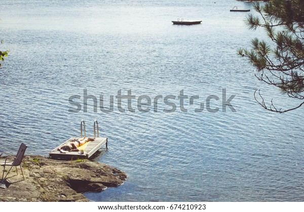 Woman tanning on dock in the summer