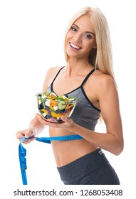 Woman with tape measure and bowl of salad, isolated against white background. Young sporty blond model at studio shot. Health, beauty and fitness concept.